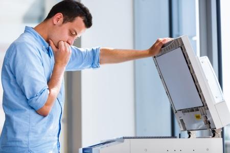 fotocopiadora: Apuesto joven utilizando una máquina de copia
