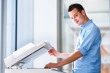 fotocopiadora: Apuesto joven utilizando una máquina de copia (DOF, imagen entonada color)