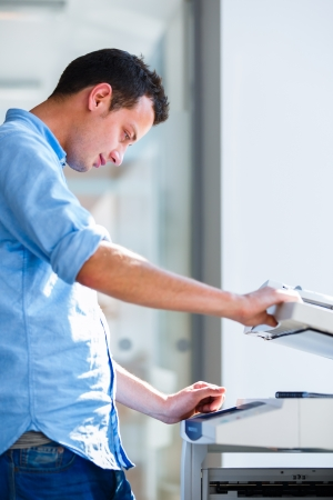 fotocopiadora: Apuesto joven utilizando una máquina copiadora DOF superficial; imagen de color entonado Foto de archivo