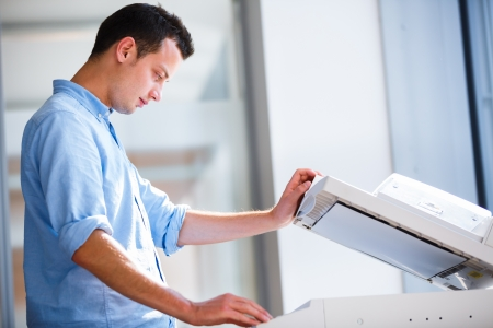 photocopy: Handsome  young man using a copy machine    Stock Photo