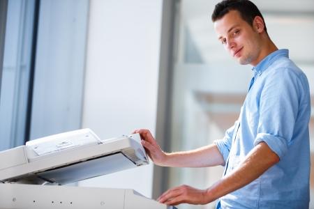 impresora: Apuesto joven utilizando una máquina copiadora DOF superficial; imagen de color entonado Foto de archivo