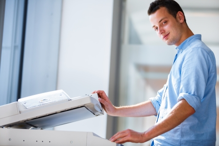 office printer: Handsome  young man using a copy machine  shallow DOF; color toned image  Stock Photo