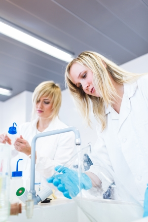 Two female researchers working in a laboratory  color toned image  photo