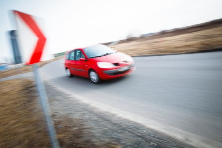 convey: Traffic concept  car driving fast through a sharp turn  motion blur is used to convey movement