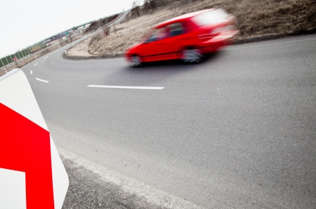sharp curve: Traffic concept  car driving fast through a sharp turn  motion blur is used to convey movement