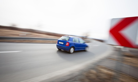 Traffic concept  car driving fast through a sharp turn  motion blur is used to convey movement  photo