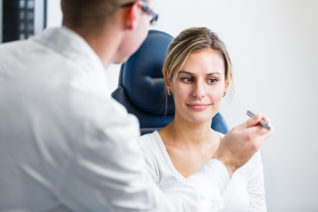 oculist: Optometry concept - pretty young woman having her eyes examined by an eye doctoroptometrist (color toned image; shallow DOF)