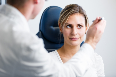 sight chart: Optometry concept - pretty young woman having her eyes examined by an eye doctoroptometrist (color toned image; shallow DOF)