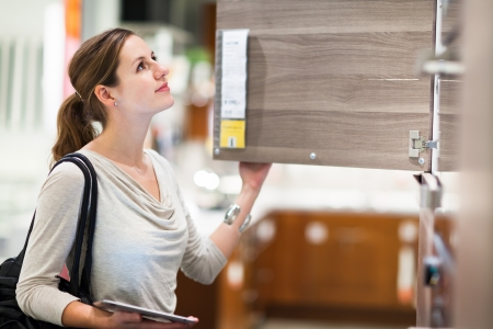 Young woman shopping for furniture in a furniture store, using her tablet computer to compare prices/check for dimensions Stock Photo - 17256228