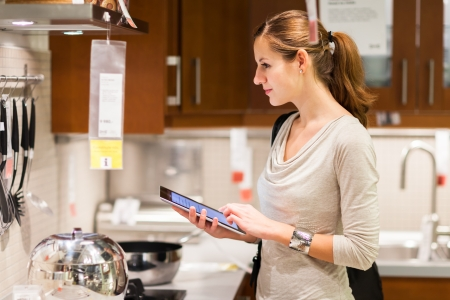 Young woman shopping for furniture in a furniture store, using her tablet computer to compare prices/check for dimensions Stock Photo - 17256238