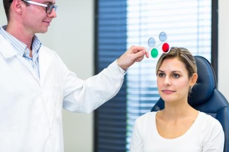 examen de la vista: Concepto de Optometr?a - mujer bastante joven que hace sus ojos sean examinados por un oftalm?logo  optometrista (imagen a color entonado, someras DOF)