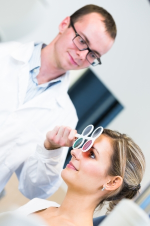 Optometry concept - pretty young woman having her eyes examined by an eye doctoroptometrist (color toned image; shallow DOF) photo