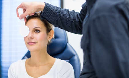 medical examination: Optometry concept - pretty young woman having her eyes examined by an eye doctoroptometrist
