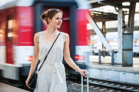 Pretty young woman at a train station photo