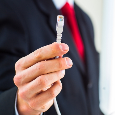 Young businessman holding an ethernet cable - stressing the importance of fast and reliable internet connection for a business color toned image; shallow DOF Stock Photo