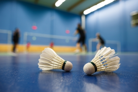 badminton racket: badminton - badminton courts with players competing; shuttlecocks in the foreground (shallow DOF; color toned image)