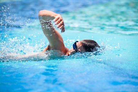 若い男がプールでクロールを泳ぐ