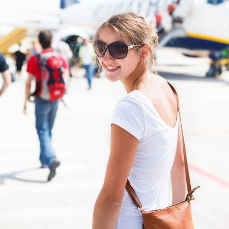 passenger aircraft: Departure - young woman at an airport about to board an aircraft on a sunny summer day Stock Photo