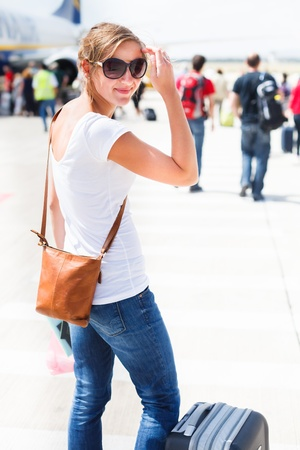 arrive: Departure - young woman at an airport about to board an aircraft on a sunny summer day Stock Photo