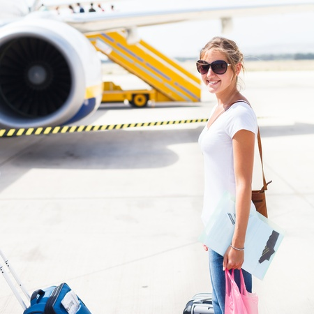 Departure - young woman at an airport about to board an aircraft on a sunny summer day photo