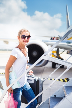 business traveler: Departure - young woman at an airport about to board an aircraft on a sunny summer day Stock Photo