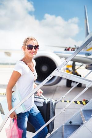 viajero: Salida - mujer joven en un aeropuerto a punto de abordar un avi?n en un d?a soleado de verano Foto de archivo