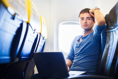 Handsome young man daydreaming while working on his laptop computer on board of an airplane during flight photo