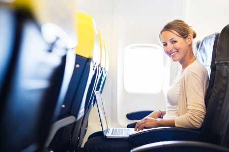 passenger vehicle: Young woman working on her laptop computer on board of an airplane during the flight