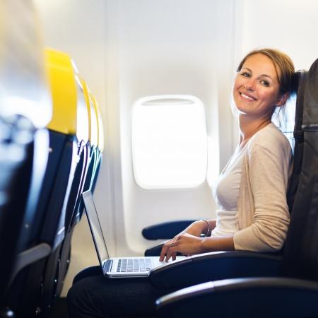Jonge vrouw die op haar laptop computer aan boord van een vliegtuig tijdens de vlucht Stockfoto