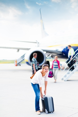 airport runway: Just arrived: young woman at an airport having just left the aircraft