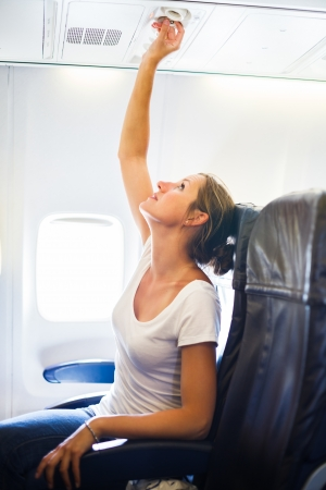 Female passenger adjusting air conditioning above her seat while on board of an aircraft Stock Photo - 17628177