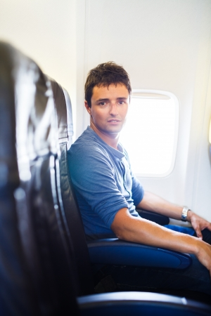 Handsome young man on board of an airplane during flight,  looking at the camera with a relaxed, confident expression photo