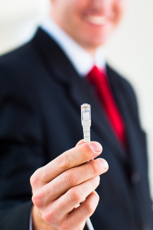 Young businessman holding an ethernet cable - stressing the importance of fast and reliable internet connection for a business Stock Photo - 17662117