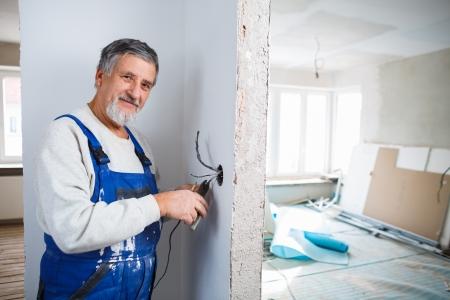 Hombre mayor que trabaja en las instalaciones eléctricas en un apartamento recién reformado