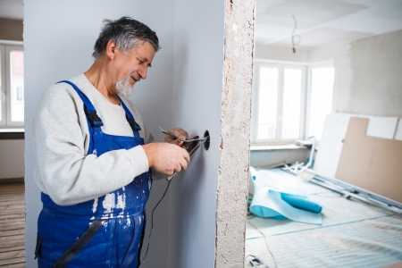 man working: Senior man working on the electrical installations in a freshly renovated appartment Stock Photo