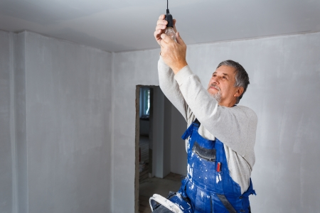 updating: Senior man installing a bulb in a freshly renovated appartment Stock Photo