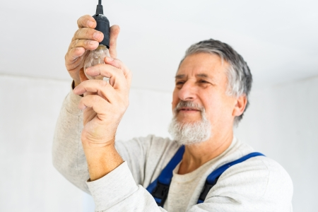 appartment: Senior man installing a bulb in a freshly renovated appartment Stock Photo