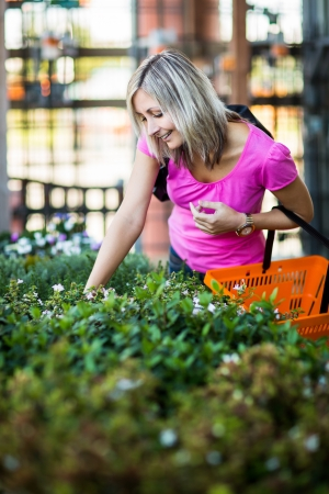 Young woman buying flowers at a garden center Stock Photo - 17692585