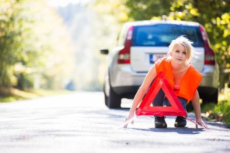 zichtbaarheid: Jonge vrouwelijke bestuurder het dragen van een hoge zichtbaarheid vest, het opzetten van de reflecterende trianglec nadat haar auto heeft opgesplitst
