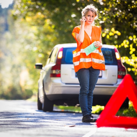 emergency vest: Young female driver wearing a high visibility vest, calling the roadside serviceassistance after her car has broken down Stock Photo