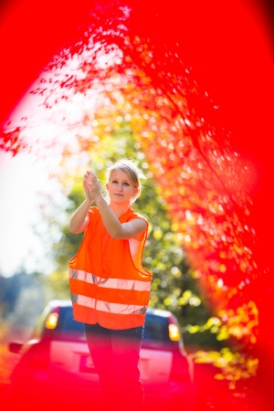 Young female driver wearing a high visibility vest on the roadside after her car has broken down photo
