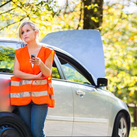 zichtbaarheid: Jonge vrouwelijke chauffeur het dragen van een hoge zichtbaarheid vest, het aanroepen van de weg-service  assistentie nadat haar auto heeft afgebroken