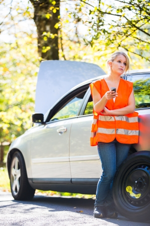 high visibility: Young female driver wearing a high visibility vest, calling the roadside serviceassistance after her car has broken down Stock Photo