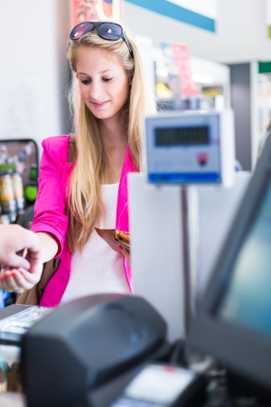 Beautiful young woman paying for her groceries at the counter of a grocery store/supermarket (color toned image) Stock Photo - 17885286