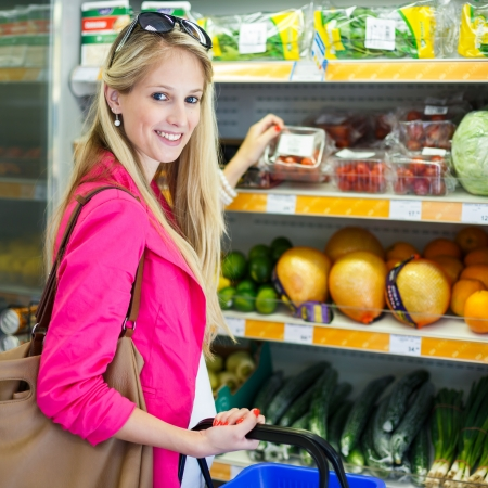 produce sections: Beautiful young woman shopping for fruits and vegetables in produce department of a grocery storesupermarket (color toned image) Stock Photo