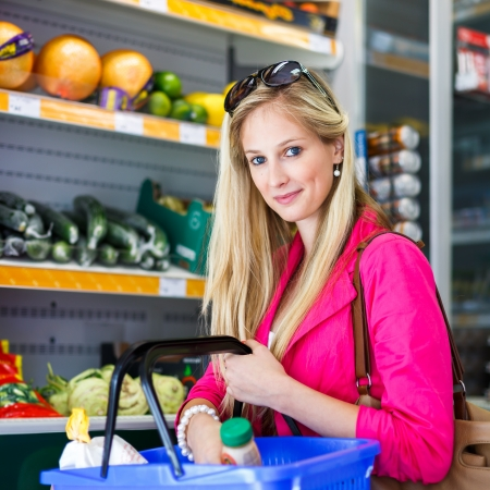 Beautiful young woman shopping for fruits and vegetables in produce department of a grocery store/supermarket (color toned image) Stock Photo - 17885329