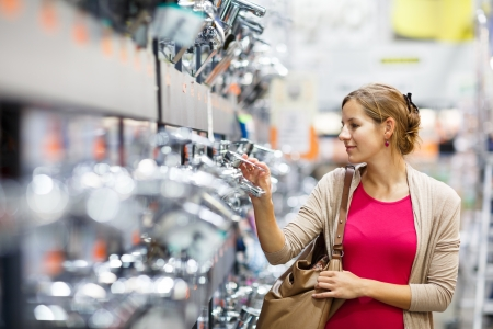furnish: Pretty young woman choosing a bathroomkitchen tap in a home furnishings retail store Stock Photo