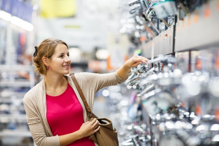 furnishings: Pretty young woman choosing a bathroomkitchen tap in a home furnishings retail store Stock Photo