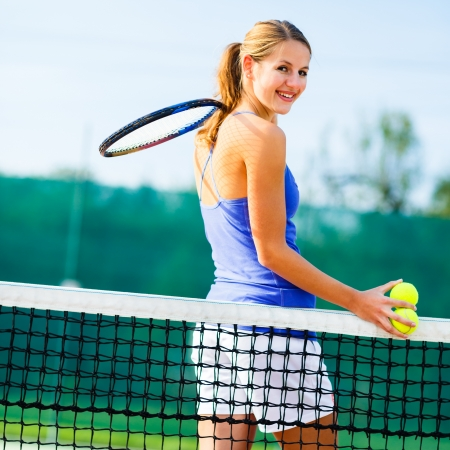 Portrait of a pretty young tennis player on the court photo