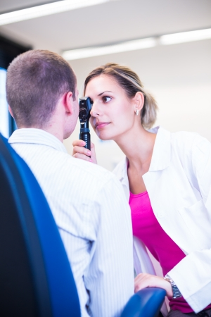eye sight: Optometry concept - handsome young man having his eyes examined by an eye doctor (color toned image; shallow DOF)